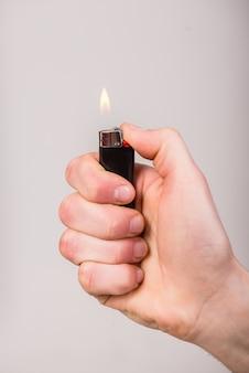 La mano maschio sta tenendo un accendino