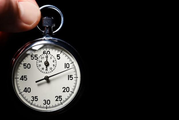 La mano maschio tiene il cronometro analogico su un fondo nero, primo piano, isolato, spazio della copia