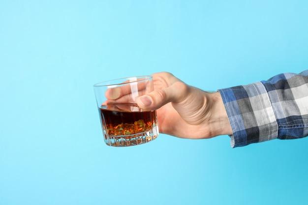 La mano maschio tiene il vetro di whiskey con i cubetti di ghiaccio su fondo blu, spazio per testo
