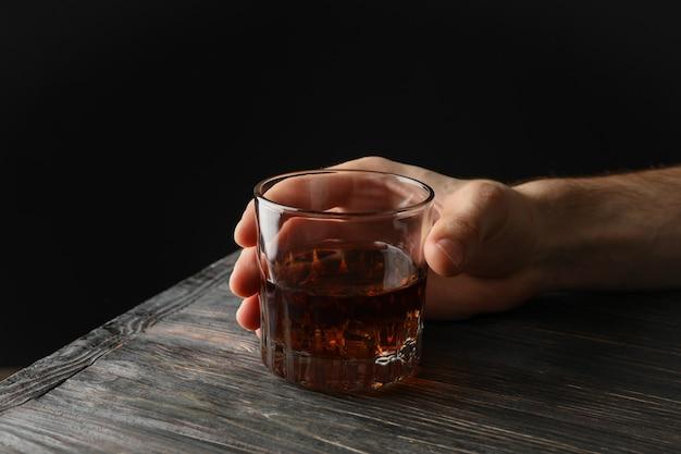 La mano maschio tiene il vetro di whiskey con i cubetti di ghiaccio su fondo di legno, spazio per testo