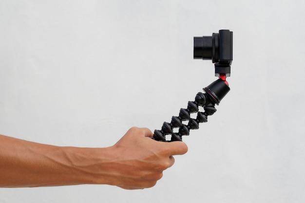 La mano maschio tiene una macchina fotografica digitale nera sul treppiede. concetto di vlog.