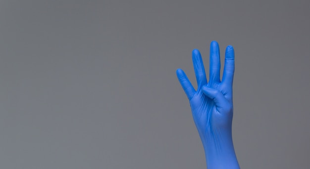 La mano nel guanto chirurgico mostra quattro dita su sfondo neutro. copia spazio