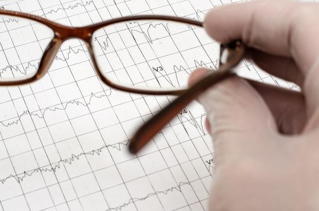 La mano nel guanto medico bianco tiene gli occhiali. electroca