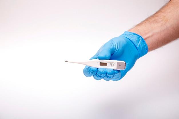 La mano nel guanto protettivo contiene termometro elettronico, siringa, mascherina chirurgica, pillole e vaccino antinfluenzale sul blu. concetto cinese di metodi di protezione del virus covid-19 del coronavirus di wuhan.