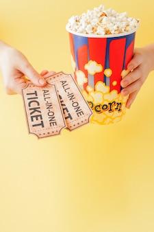 La mano prende biglietti per un film e popcorn da un bicchiere di carta