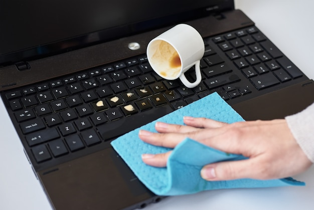 La mano pulisce il caffè rovesciato sulla tastiera del computer portatile con lo straccio