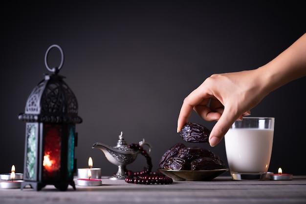 La mano raggiunge un piatto con i frutti della data