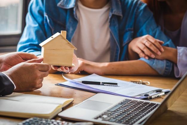 La mano rappresentativa di vendita del primo piano offre il modello di legno della casa alle giovani coppie asiatiche