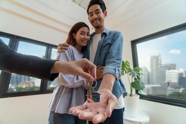 La mano rappresentativa di vendita del primo piano offre la catena chiave della casa alle giovani coppie asiatiche