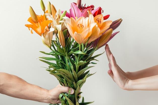 La mano regala un mazzo di fiori di gigli a una ragazza, la donna rifiuta e mostra il segnale di stop