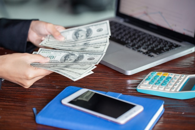 La mano riconta i dollari. la donna conta i soldi nuove banconote da cento dollari