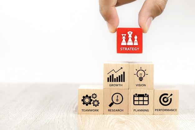 La mano sceglie il blog del giocattolo di legno del cubo con l'icona di strategia aziendale.