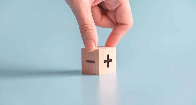 La mano sceglie il blog di legno con più e meno su fondo blu.