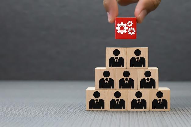 La mano sceglie l'icona degli ingranaggi sul blocco di legno per lavoro di squadra.