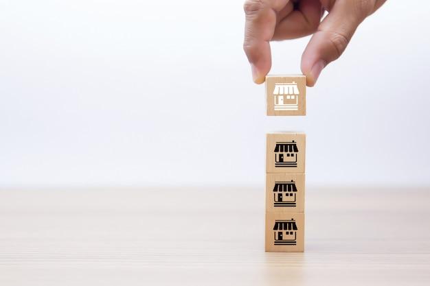 La mano sceglie le icone di affari di franchising deposito sul blocco di legno