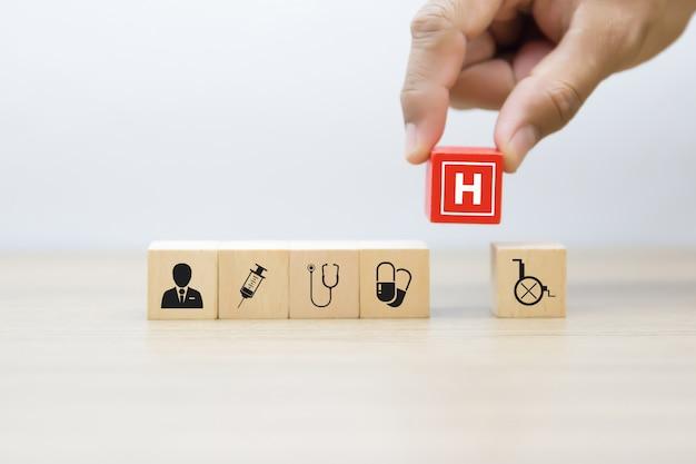 La mano sceglie le icone mediche e di salute sul blocco di legno.