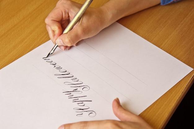 La mano scrive con la penna inchiostro la felice halloween su un foglio di carta bianca con strisce.