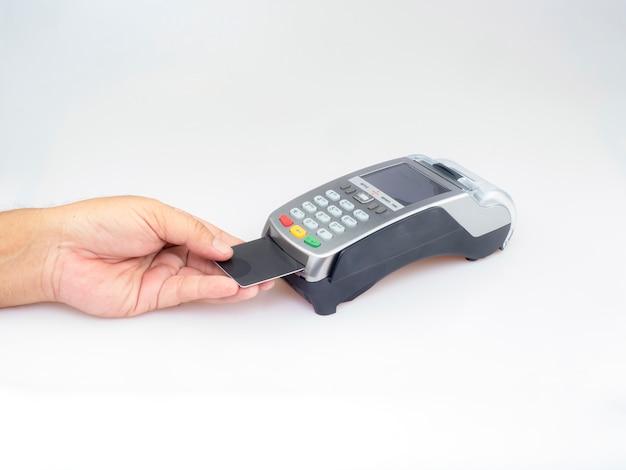 La mano spinge la carta in bianco nera dentro alla carta di credito