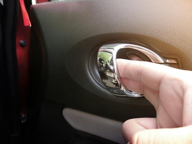 La mano sta aprendo la maniglia della porta all'interno dell'auto.