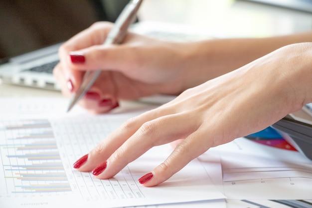 La mano sta indicando i dati del rapporto sulla tabella.