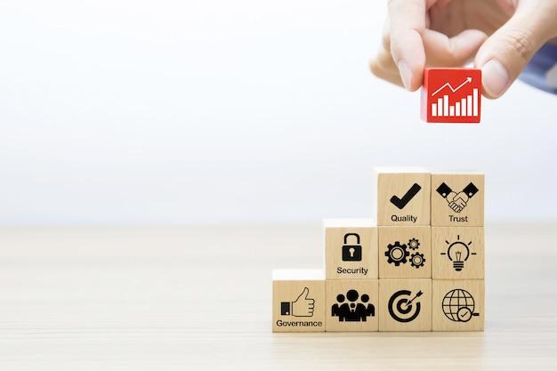La mano sta scegliendo l'icona grafica del grafico sul blocco di legno.