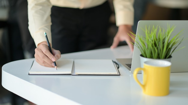 La mano sta scrivendo una nota su un taccuino con una tazza di caffè e un computer portatile sulla scrivania.