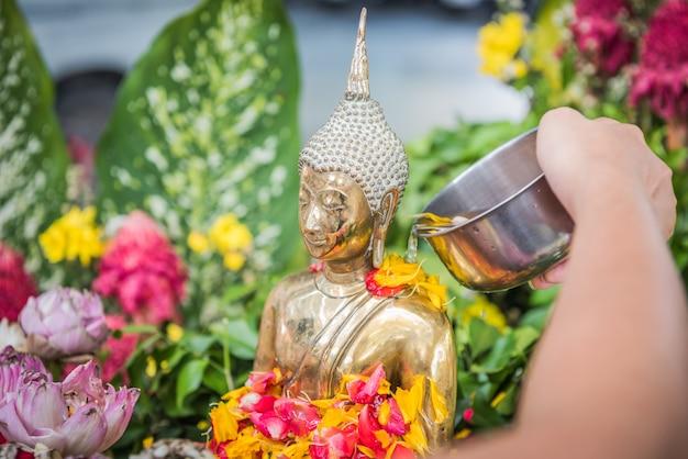 La mano sta versando acqua sulla statua del buddha in occasione del giorno del festival di songkran