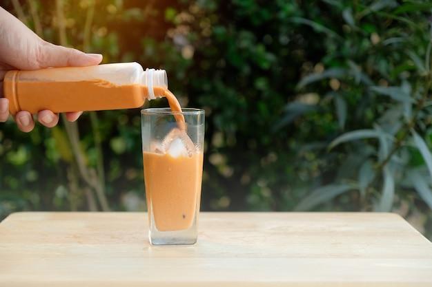 La mano sta versando il tè tailandese freddo da una bottiglia nel bicchiere con ghiaccio.
