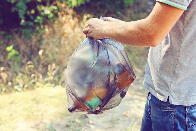La mano tiene contro una foresta piena di immondizia un grande sacchetto di plastica nera, un giorno d'estate