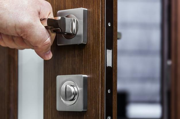 La mano tiene e apre una maniglia della porta