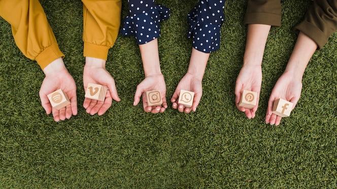 La mano tiene i blocchi di legno delle icone di app di media sociali su erba verde