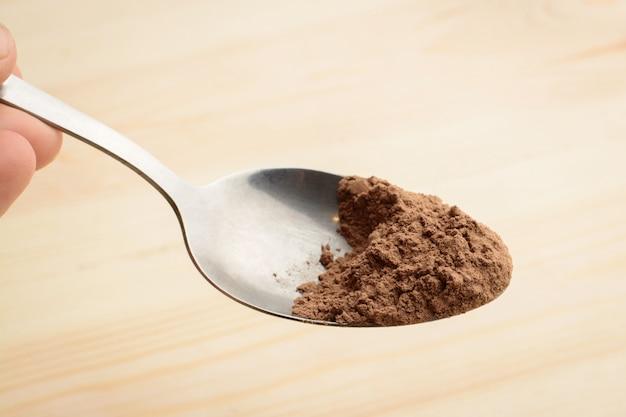 La mano tiene il cucchiaio con cacao in polvere sopra la tavola di legno in cucina