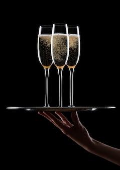 La mano tiene il vassoio con bicchieri di champagne gialli