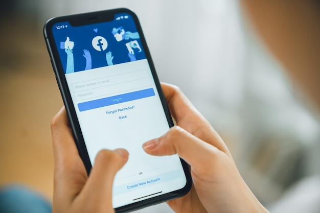 La mano tiene lo smartphone e lo schermo di facebook