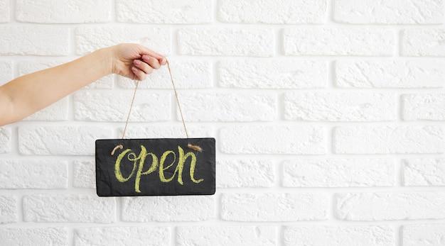 La mano tiene un cartello che dice aperto sul bar o ristorante appendere alla porta all'ingresso. dopo la quarantena. apertura commerciale