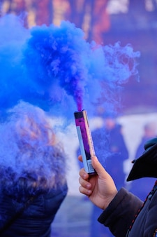 La mano tiene un fuoco d'artificio con un fumo del colore blu in una folla di persone