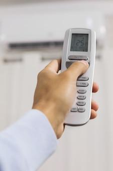 La mano tiene un telecomando del condizionatore d'aria