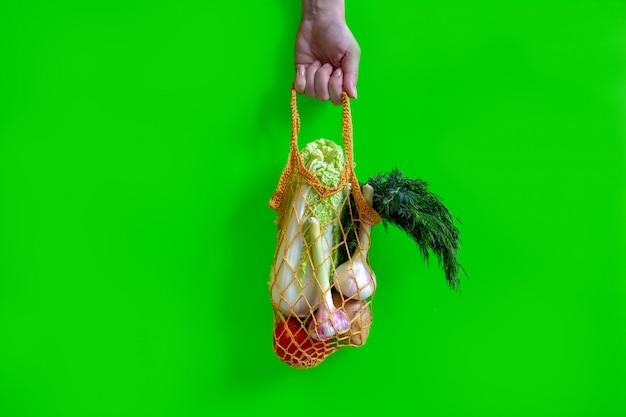 La mano tiene una borsa a maglia con verdure: pomodori, aglio, patate, cavoli, cipolle