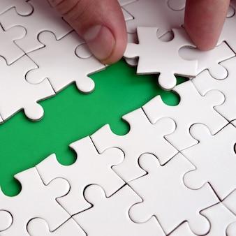 La mano umana apre la strada alla superficie del puzzle, formando uno spazio verde.