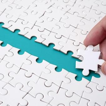 La mano umana apre la strada verso la superficie del puzzle