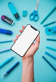 La mano umana che tiene il cellulare dello schermo bianco sopra cancelleria ha sistemato nella forma circolare sul contesto blu