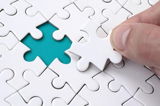 La mano umana riempie gli ultimi elementi mancanti della superficie dal puzzle