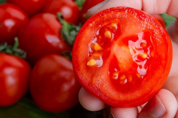 La mano umana tiene un pomodoro a fette su un tavolo dove giacciono pomodori ciliegia rossi maturi.
