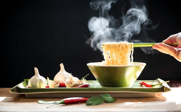 La mano usa le bacchette verdi per raccogliere gli spaghetti. concetto di cibo spazzatura