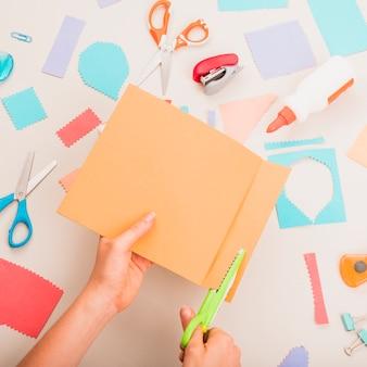La mano variopinta della persona che taglia la carta sopra i rifornimenti di scuola sulla tavola