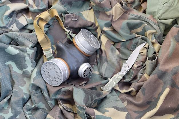 La maschera antigas sovietica dei soldati stalker giace con un coltello su giacche mimetiche verde kaki