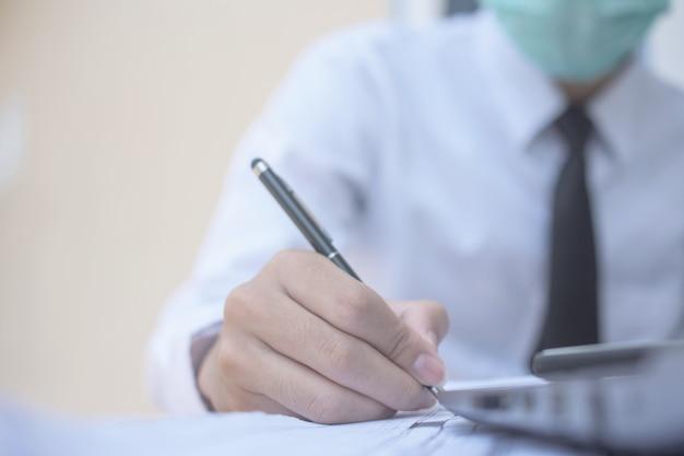 La maschera chirurgica di uso dell'uomo d'affari e lavorare nell'ufficio quindi scrive sul documento di affari