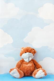 La maschera di influenza d'uso dell'orsacchiotto si siede sul fondo del cielo blu. concetto malato o inquinamento ambientale, inquinamento gassoso.
