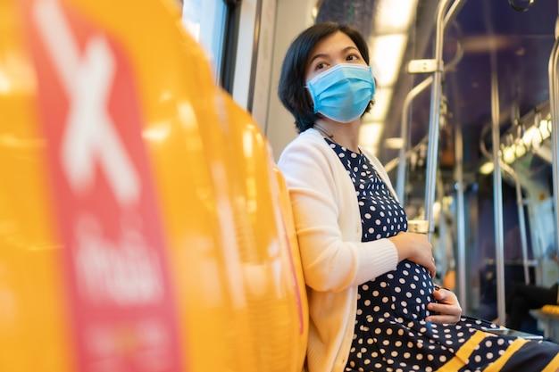 La maschera di protezione asiatica di usura della donna incinta si siede in treno di alianti nella nuova vita normale
