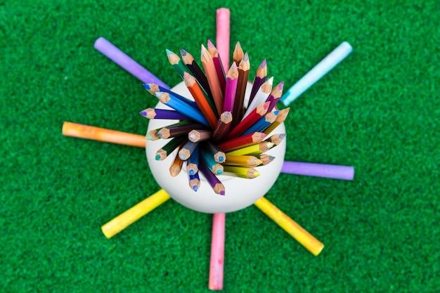 La matita ha messo nella vista superiore del piccolo barattolo su erba verde di nuovo al concetto della scuola